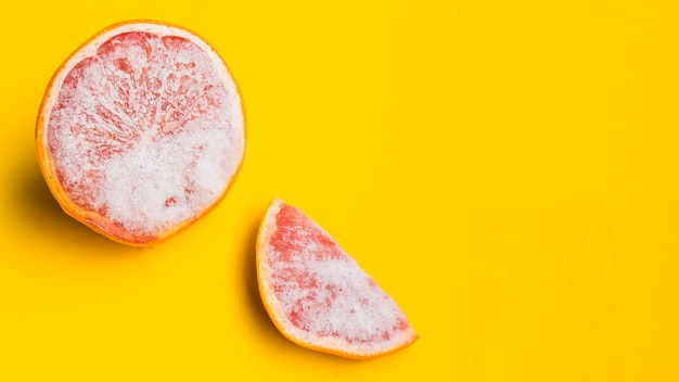 Frozen grapefruit on yellow background