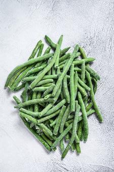 Замороженные зеленые бобы на белом кухонном столе