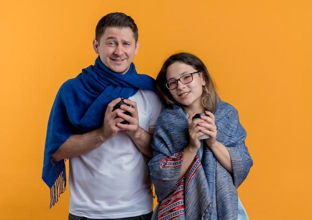 オレンジ色に笑みを浮かべてコーヒーカップを保持している暖かい毛布に包まれた凍った幸せな若いカップルの男性と女性