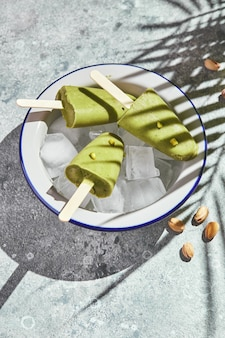 Frozen homemade pistachio popsicle in bowl of ice