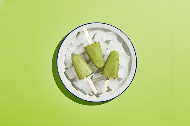 氷のボウルに冷凍自家製ピスタチオ アイスキャンディー