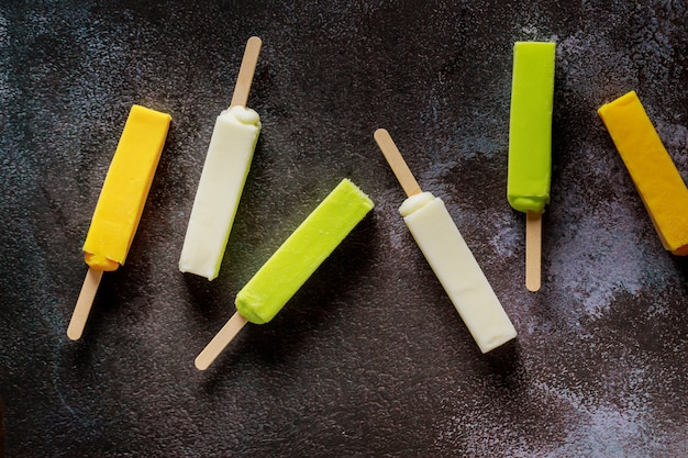 暗い表面に冷凍アイスクリームフルーツアイスキャンデー