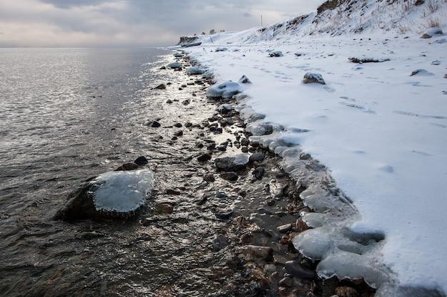 Замерзший лед на камнях в воде у берега зимой. пасмурный день. отраженный свет блестит на воде. снег на берегу.