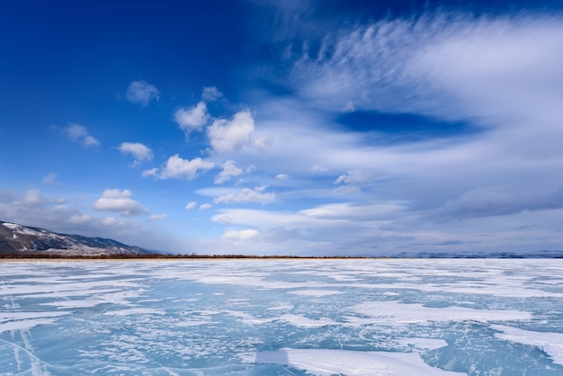 Frozen lake baikal. beautiful stratus clouds over the ice surface on a frosty day.