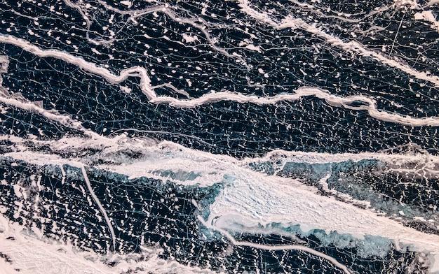 Frozen lake baikal top view. ice, cracks, snow, shore, trees. irkutsk region, russia