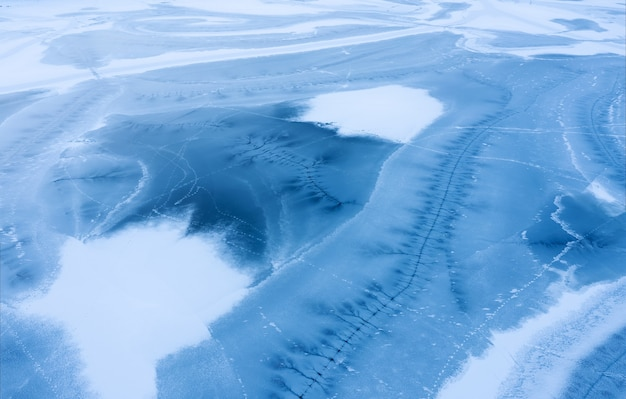Frozen lake surface covered with snow with cracks in the ice. aerial view.