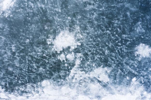 凍った湖のテクスチャの背景。氷と雪で覆われた水面。