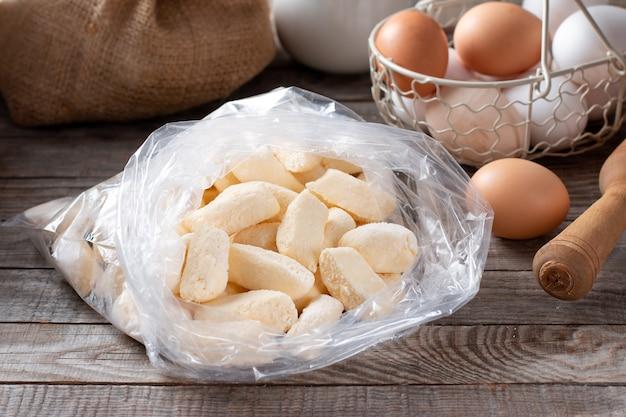 Замороженные ленивые пельмени, творожные «ленивые» пельмени в мешочке на деревянном столе.