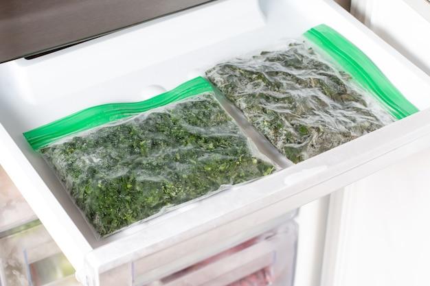 Замороженные листья базилика в морозилке. замороженные овощи. концепция здорового питания.