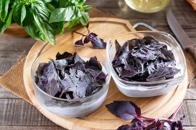 Замороженные листья базилика со свежим базиликом на деревянном столе. замороженные овощи. концепция здорового питания.