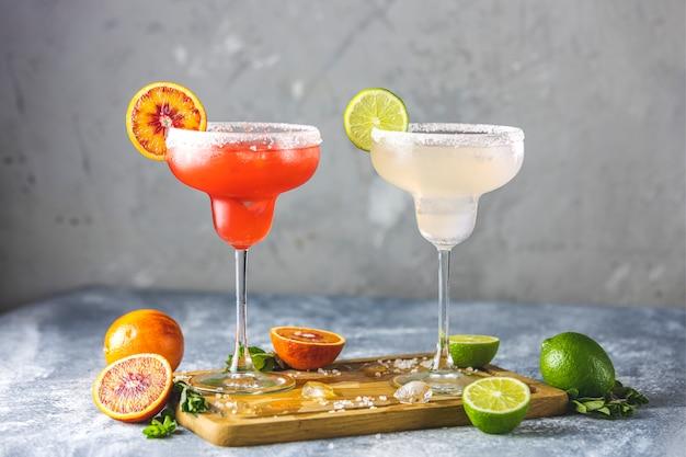 Frozen lime margarita and blood orange margarita cocktail mix in salt rimmed glasses garnished