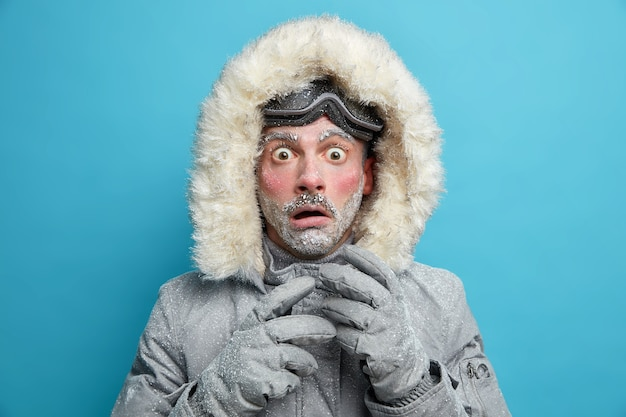 L'esploratore maschio congelato ha la faccia rossa ricoperta di brina guarda molto scioccato sorpreso dalla temperatura molto bassa indossa una giacca calda e guanti cammina all'aperto durante la bufera