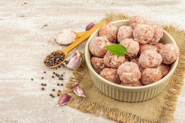 セラミックボウルにスパイス、バジルの葉、ニンニクのクローブを入れた冷凍ミートボール。食品を調理するための原材料。木製の背景、コピースペース