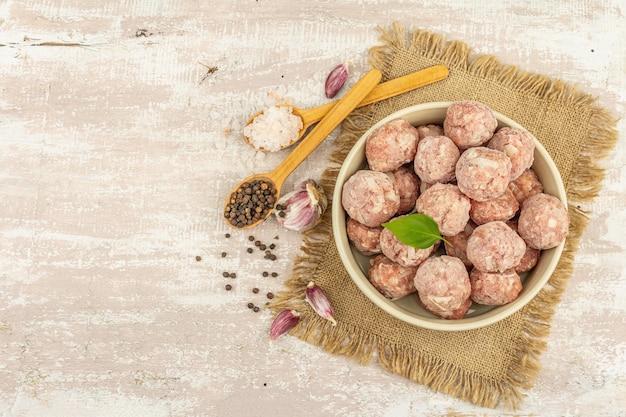 セラミックボウルにスパイス、バジルの葉、ニンニクのクローブを入れた冷凍ミートボール。食品を調理するための原材料。木製の背景、上面図