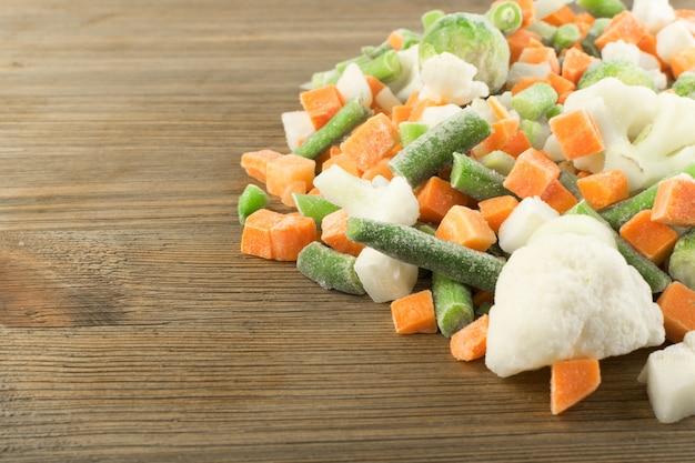 木製のテーブルの上の冷凍混合野菜。生のみじん切り、カリフラワー、タマネギ、インゲン、芽キャベツ