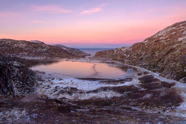 峡谷の凍った山の湖。狭い道が湖の周りに続いています。北極の夕日の山の風景。