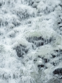 Замерзший горный водопад. водопад со льдом. зимний фон. вертикальный вид.