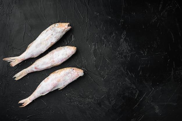 冷凍ボラまたはスルタンカの魚のセット、黒い暗い石のテーブル