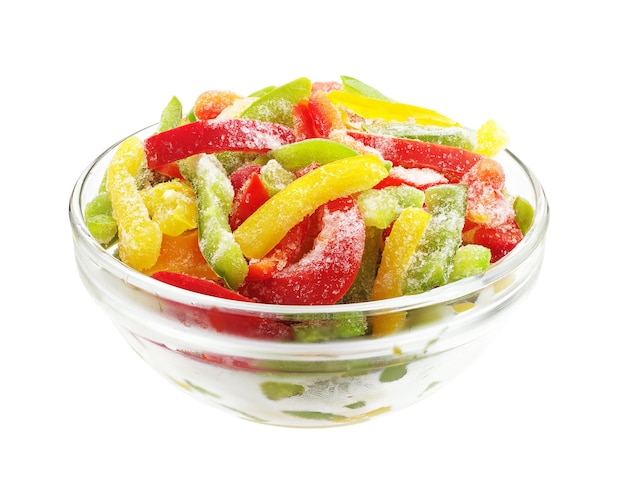 Frozen multicolored peppers slices in glass bowl isolated on white background Premium Photo