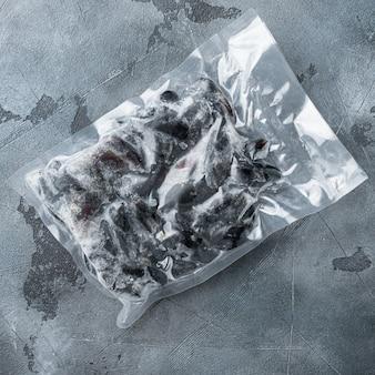 灰色の背景に、サッシセットで冷凍ムール貝