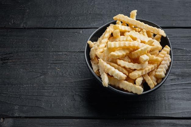 Замороженные чипсы из духовки, нарезанный картофель, на черном фоне деревянного стола, с copyspace и местом для текста
