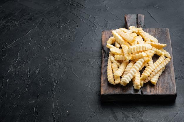 Замороженные чипсы из духовки, нарезанный картофель, на деревянной разделочной доске, на черном фоне, с copyspace и местом для текста
