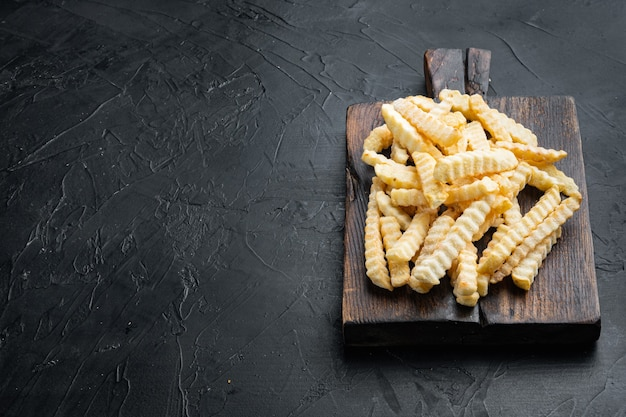 Frozen oven chips sliced potato set, on wooden cutting board, on black background , with copyspace  and space for text