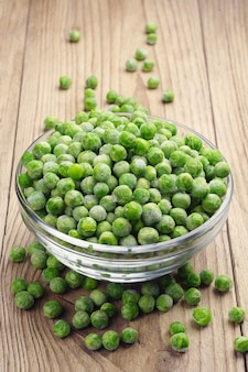 Frozen peas in a glass bowl on a wooden table