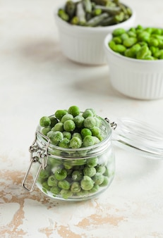 ガラスの瓶に冷凍エンドウ豆。冷凍は、栄養価の高い食品の貯蔵寿命を延ばす安全な方法です。