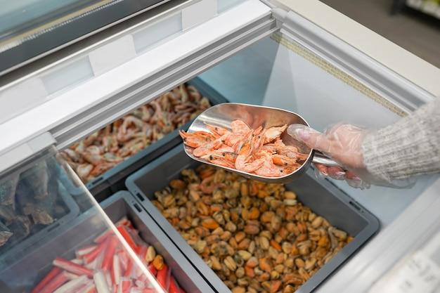 상자에 냉동된 분홍색 생새우. 여자 손에는 신선한 새우가 있습니다. 익히지 않은 껍질을 벗기지 않은 해산물