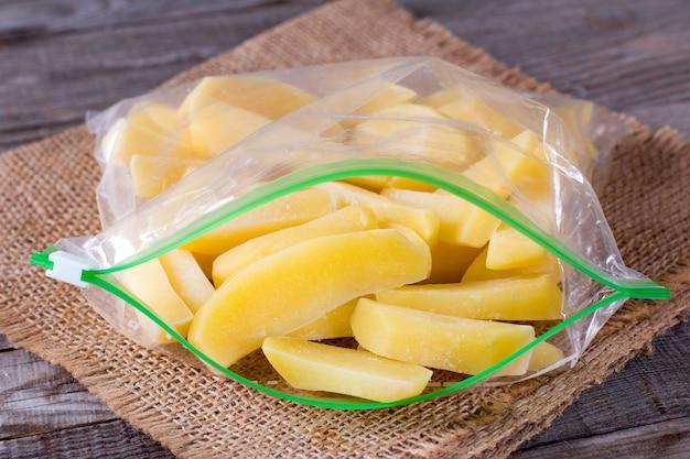 木製のテーブルの上の袋に冷凍ジャガイモ