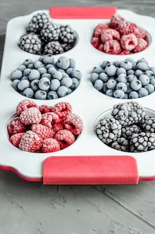 冷凍ラズベリー、ブルーベリー、コンクリートの背景が灰色の白い鉄のグラタン皿にブラックベリー。