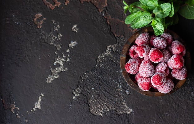 Frozen raspberries in a coconut shell and mint on a dark brown stone background