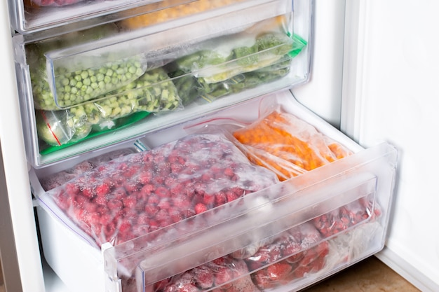 Frozen raspberries and sea buckthorn in the freezer. frozen berries. food storage