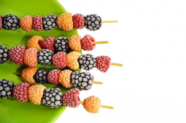 Замороженные ягоды малины и ежевики на деревянных шпажках на зеленой тарелке Premium Фотографии