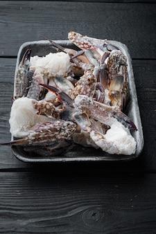 黒い木製のテーブルの上に、冷凍生の青鯛の肉セット、プラスチック トレイ