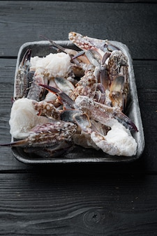 Frozen raw blue swimming crab meat set, in plastic tray, on black wooden table