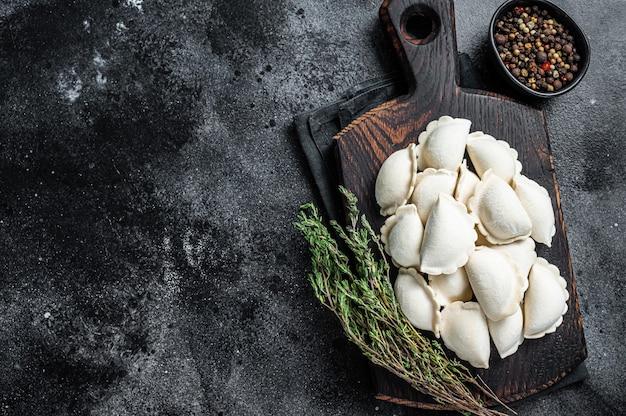 Frozen raw dumplings pierogi with potato on a wooden board.   top view.