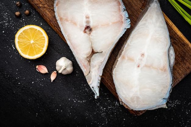 Замороженный стейк из сырой рыбы на деревянной разделочной доске со специями на черном фоне.
