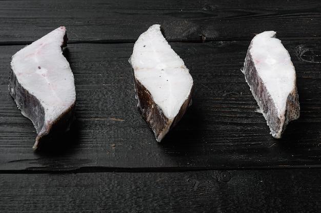 검은색 나무 테이블 배경에 있는 냉동 생선 스테이크 세트, 텍스트 복사 공간