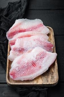 Замороженное сырое мясо рыбы тилапии, на черном деревянном столе