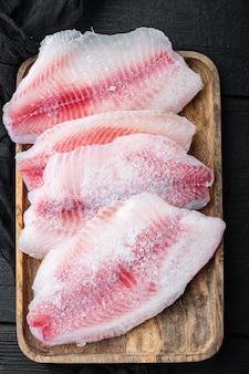 Замороженное сырое мясо рыбы тилапии, на старом деревянном столе, вид сверху
