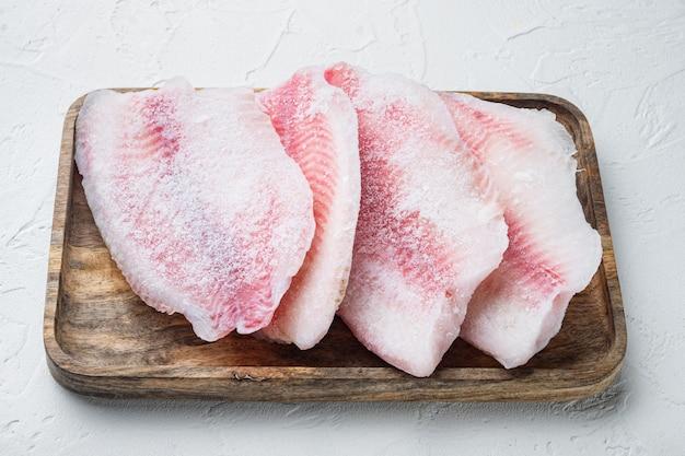 Замороженное сырое мясо рыбы тилапия, на белом столе