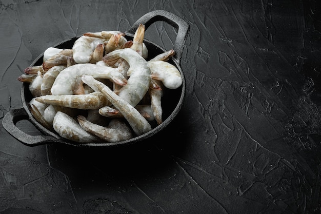 Frozen raw uncooked tiger prawns, shrimps set, in cast iron frying pan, on black stone background, with copy space for text