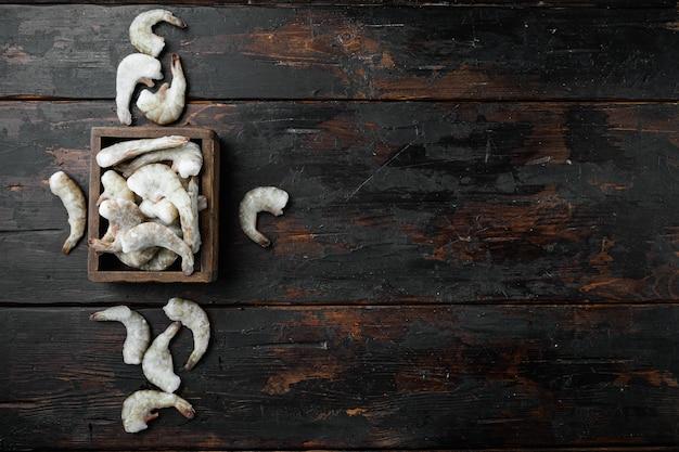 冷凍生の未調理のタイガーエビ、エビのセット、古い暗い木製のテーブル、上面図フラットレイ