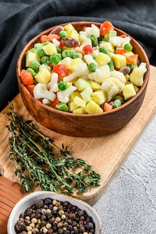 Frozen raw vegetables in a wooden bowl.