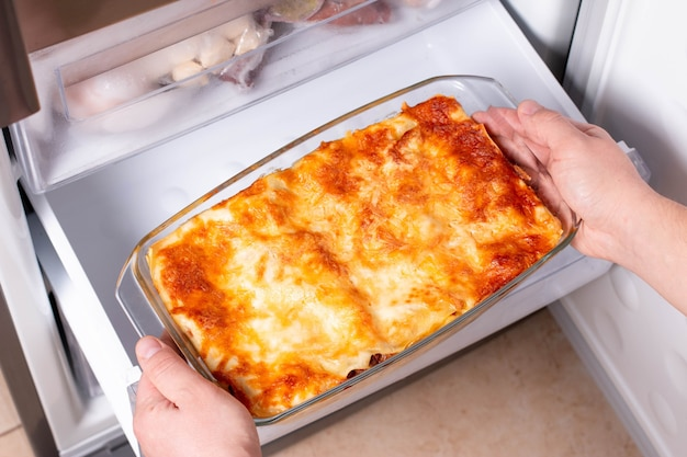 Frozen ready meals. man's hands are taking frozen lasagna from the freezer of the fridge. concept of ready made frozen dishes and saving time on cooking food.