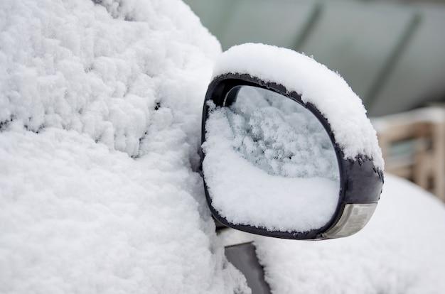 Frozen rearview mirror, snowy car. winter, snow, snowfall