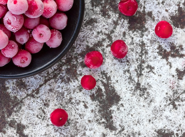 Frozen red cherries on the white surface of the old shabby.