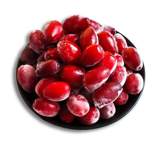 Замороженные красные плоды кизила на белом фоне